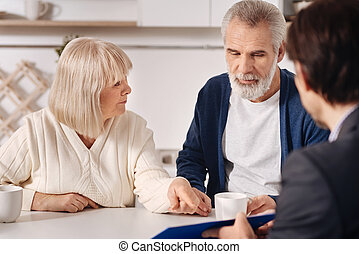 Optimistic senior couple having conversation with advisor at home