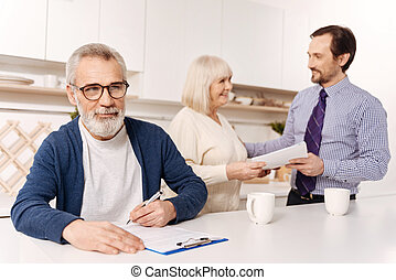 Bearded man signing agreement while his wife meeting notary...