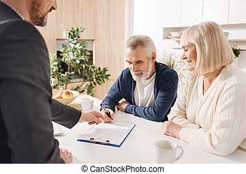 Benevolent old couple signing mortgage agreement at home