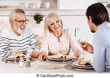 Cheerful family sitting at the dinner table in the kitchen -...