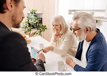 Ambitious real estate agent working with retired couple of...