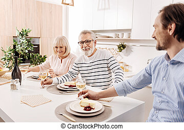 Positive elderly parents enjoying weekend with son at home -...