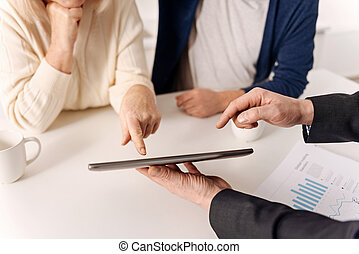 Helpful real estate agent working with aging couple of...