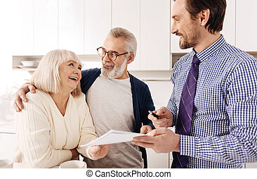 Upbeat old couple consulting with financial adviser at home
