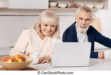 Delighted aged couple using laptop at home - Getting...