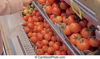 a woman chooses tomatoes in the store.