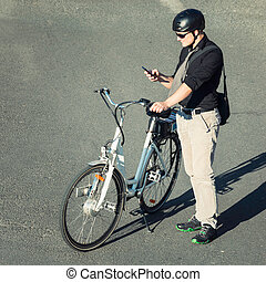 High angle view of businessman with electric bibycle using cell phone
