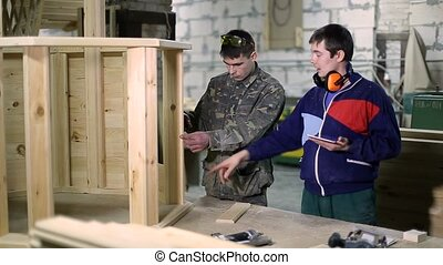 Carpenters using digital tablet in workshop - Skilled...
