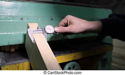 Carpenter with calipers measuring wood in workshop -...