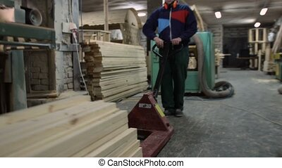 Carpenter working with manual forklift pallet - Carpenter...