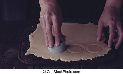 Making shortbread cookies by woman's hands over old wooden...