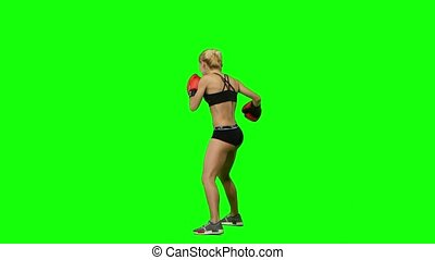 Boxer standing in the front and make swings and kicks. Green screen. Side view