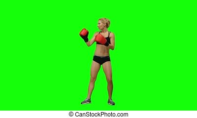 Girl kickboxer jumps up and makes swings and kicks. Green screen. Side view