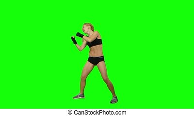 Girl kickboxer wearing gloves practicing for competitions. Green screen. Side view