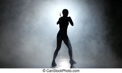 Girl kickboxer gloves sends the punches. Silhouette. Black...
