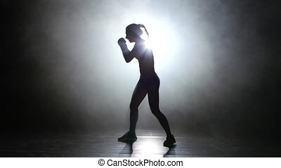 Champion boxer sends the punches. Silhouette. Light from...