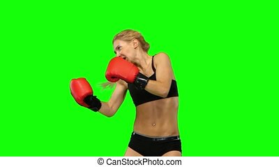 Girl boxer in red gloves beats sends alternating hands. Green screen. Side view