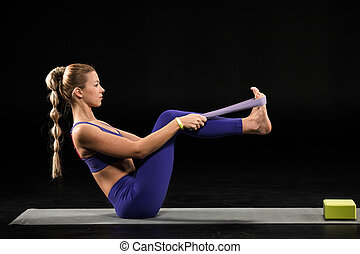 Woman practicing yoga performing boat position with yoga...