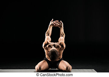 Man sitting in yoga position - Young man performing...
