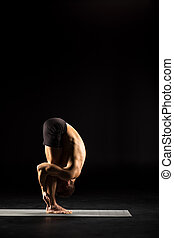 Man standing in yoga position - Man performing Uttanasana on...