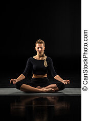 Young woman sitting and meditating - Young woman performing...