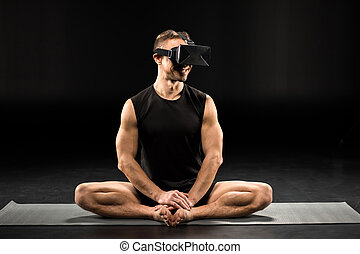 Man in virtual reality glasses sitting in Bound Angle pose...