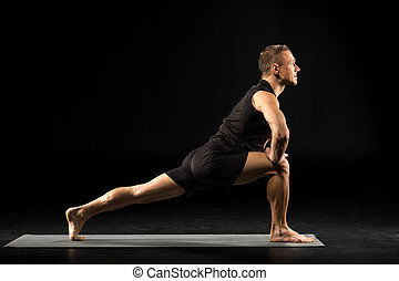Man standing in yoga position - Side view of young man...