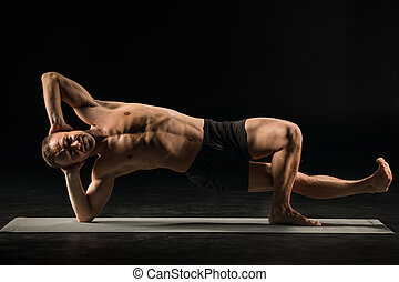 Man standing in yoga position - Athletic man practicing yoga...
