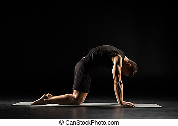 Man standing in yoga position - Man practicing yoga...