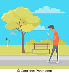Boy with Smartphone on Walk in Park out of Town - Boy looks...