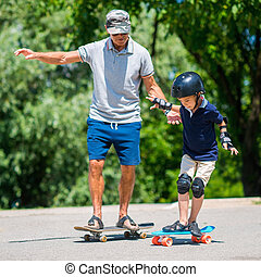 Senior man with little boy skateboarding in park