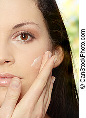 Body care - Beautiful young woman with cream.