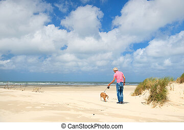 Man with dog at the beach - Man walking the dog at the beach