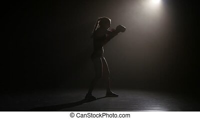 Champion boxer sends the punches. Silhouette. Lights rear....