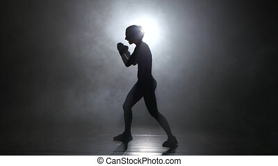 Champion kickboxer sends the punches. Silhouette. Lights...