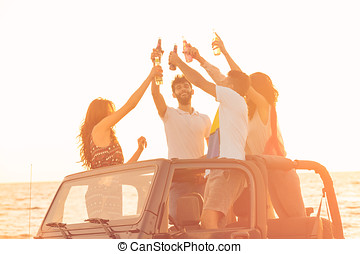 Five young people having fun in convertible car at the beach...