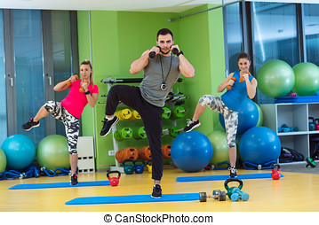 group of people working out in a gym with a dumbbell.