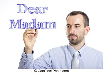 Dear Madam, - Young businessman writing blue text on...