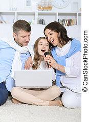 Family with daughter singing karaoke