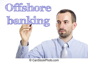 Offshore banking - Young businessman writing blue text on transparent surface