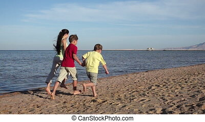 Group of three kids running away at the beach in Egypt resort