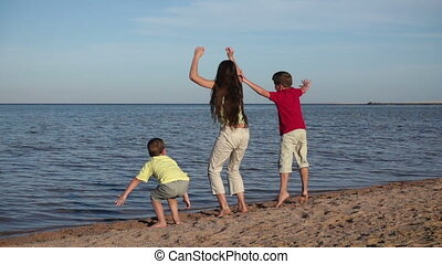 Group of three kids jumping at the beach in Egypt resort,...
