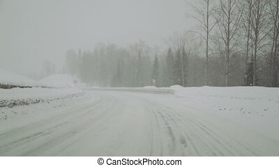 car road covered by heavy snow in winter day, winter woods