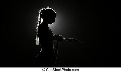 Boxer shakes special bandages on his hands. Silhouette. Black background . Side view. Close up. Slow motion
