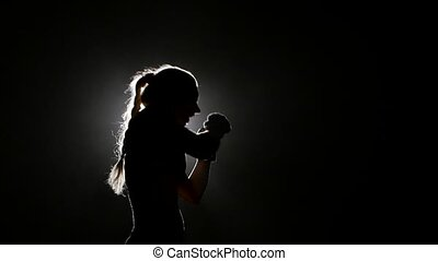 Girl sends a boxer hitting opponent. Silhouette. Black...