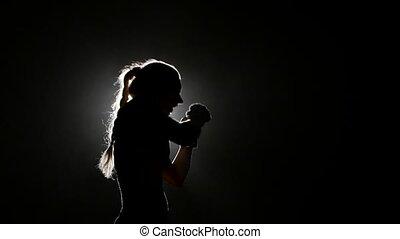 Girl sends a boxer hitting opponent. Silhouette. Black...