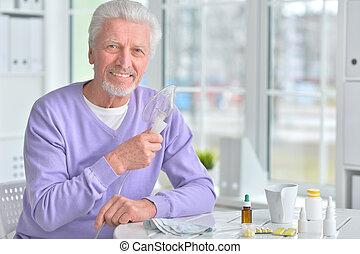 Elderly man doing inhalation