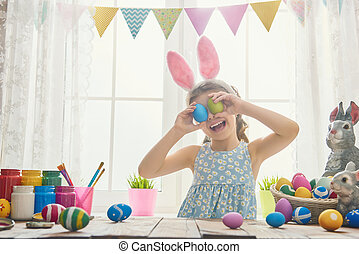 girl wearing bunny ears - Beautiful child painting eggs....