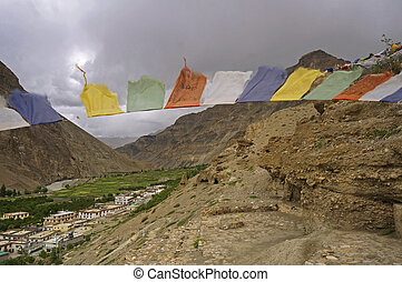 Ancient Buddhist Caves and Prayer Flags in the High-Altitude Mountain Desert in the Himalayas