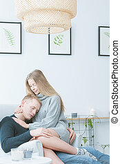 Young couple hugging each other while sitting on the...